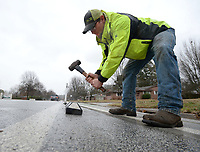 NWA Democrat-Gazette/ANDY SHUPE<br /> Ty Turner, an asphalt maintenance worker with the city of Fayetteville's Transportation Division, uses a hammer Wednesday, March 13, 2019, to reset a curb stop that had been struck by a car as he and other crew members make repairs and adjustments to a bike lane on Rolling Hills Drive in Fayetteville. The lane was constructed by Bike NWA through grant funding from the Walton Family Foundation. City workers were removing curb stops that were near driveways and intersections to make travel easier as well as resetting reflective markers.