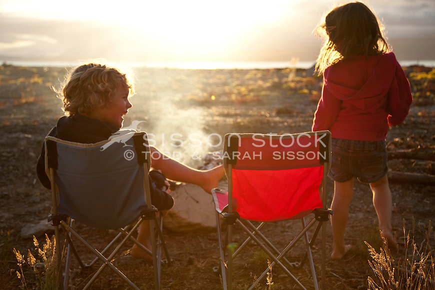 Two Children Toasting Marshmellows And Sitting In Camping Chairs In Front  Of A Campfire, New