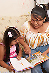 3 year old girl with mother looking at picture book