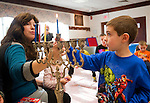 PROSPECT,  CT-122716JS02-- Nathan Ober, 5, of Naugatuck, whit the help of Dini Druk of Woodbridge, lights the Menorah during Hanukkah story hour Tuesday at the Prospect Public Library. The program included Hanukkah stories, Menorah lighting, Hanukkah sing-along and Hanukkah crafts. <br /> Jim Shannon Republican-American