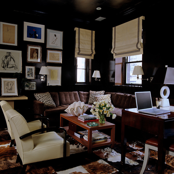 A collection of figurative and abstract drawings are displayed on the chocolate brown lacquered walls of the study