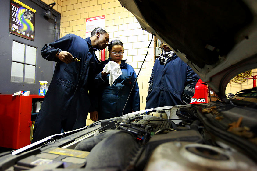 Automotive HS, Brooklyn, NY on Friday, January 22, 2010.  High school students have the opportunity to participate in a special program where they perform basic maintenance and repairs on privately owned cars at very competitive prices.  (l. to r.):  Students Patrick Grant, 18; Naomi Saez, 17; and Kenny Ramdwar, 17, check the oil.