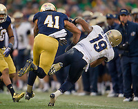 Navy QB Keenan Reynolds (19) is tackled by Irish safety Matthias Farley (41) in the second quarter at Notre Dame Stadium. Notre Dame was penalized for unnecessary roughness on the play.