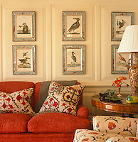 A collection of ornithological prints in beautiful frames is displayed on the living room wall