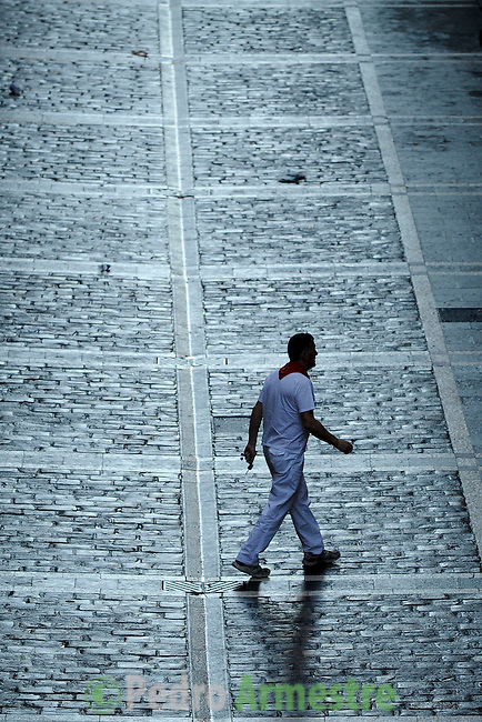 Participant walks down the Estafeta street before the first bull run of the Alcurrucen's bulls of the San Fermin Festival, on July 7, 2013, in Pamplona, northern Spain. The festival is a symbol of Spanish culture that attracts thousands of tourists to watch the bull runs despite heavy condemnation from animal rights groups. AFP PHOTO/ PEDRO ARMESTRE