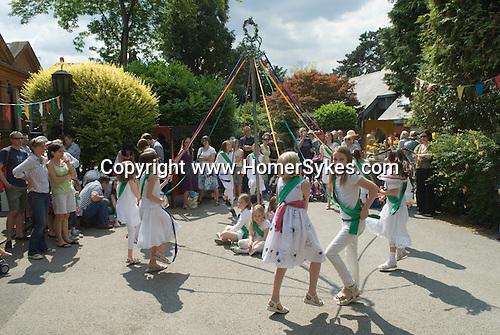 Children dancing around a May Pole Petersham village fete Richmond Surrey UK. Middle class white anglo saxon Britain.