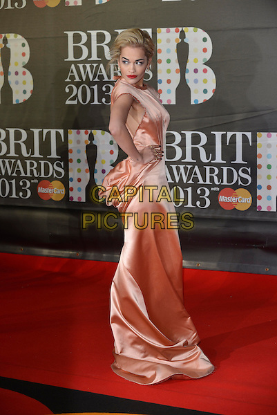 Rita Ora.The Brit Awards 2013 arrivals at the O2, Greenwich, London, England 20th February 2013.The Brits  full length peach dress silk satin halterneck ruched long maxi hand on hip gold side  train.CAP/PL.©Phil Loftus/Capital Pictures.