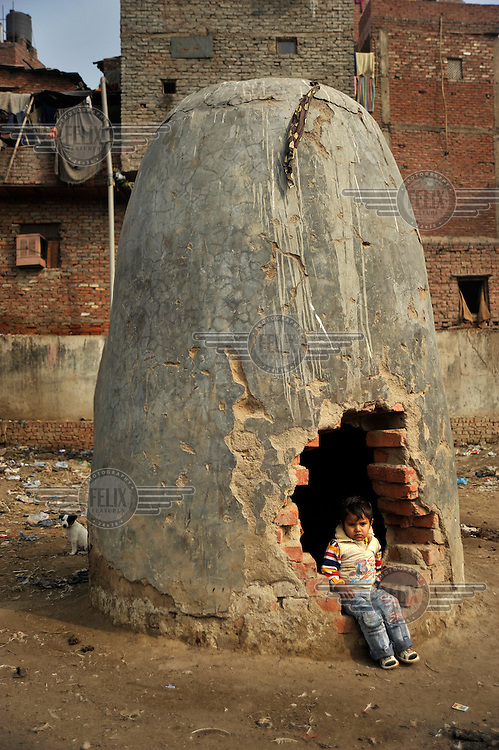 A small child sits in a gap of a broken turret in a slum in the area of Nizamuddin East.
