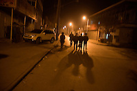 People walk along a street separating the Old Town of Kashgar from new developments in Kashgar, Xinjiang, China.