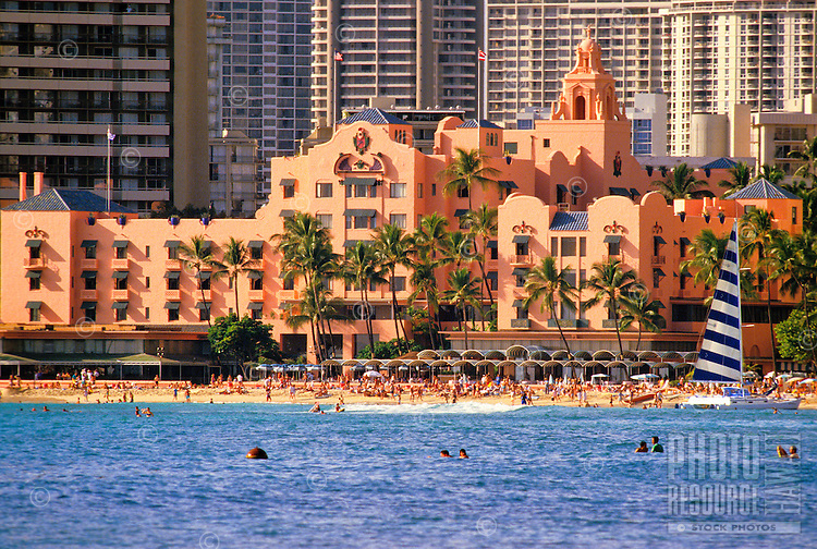 """The Royal Hawaiian Hotel or """"""""pink palace"""""""", shot from the ocean with hundreds of tourists on the beach and a blue and white striped catamaran on the beach."""