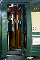 Travelling in style on the Eastern & Oriental Express from Bangkok to Singapore. Stewards waiting to welcome guests on board at Kanchanaburi Station.