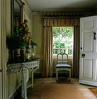 The entrance hall of the Tudor property has a castellated curtain pelmet which was designed by John Fowler