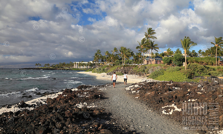 Couple walk on the King's Highway toward the Hilton Waikoloa Village, Big Island of Hawai'i.