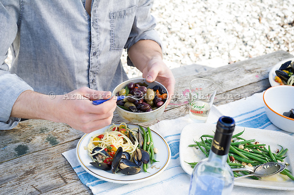 Closeup of a man's torso and hand at a picnic table, serving olives onto a plate of mussels, linguine, and string beans.