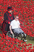 London, UK. 30 July 2014. A Yeoman Warder pushes Anthony Cooper, a double amputee serviceman who served in Helmand Province in 2010 who is one of the volunteers planting flowers. A field of ceramic poppies is being planted by volunteers in the moat of the Tower of London. It will finally consist of 888,246 poppies, each representing a British or Colonial soldier fallen during the First World War.