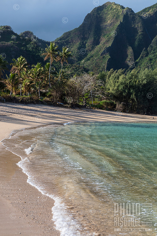 A view of the beach, mountains. and clear water at Tunnels beach on the north shore of Kaua'i.