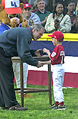 United States President George W. Bush gives a souvenir baseball to an unidentified member of the Capitol City Little League Rockies following the first t-ball game on the South Lawn of the White House in Washington, DC on May 6, 2001.<br /> Credit: Ron Sachs / CNP