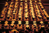 High School Graduation Ceremony, overhead sepia-toned, rear view of students seated, wearing mortarboards, education.
