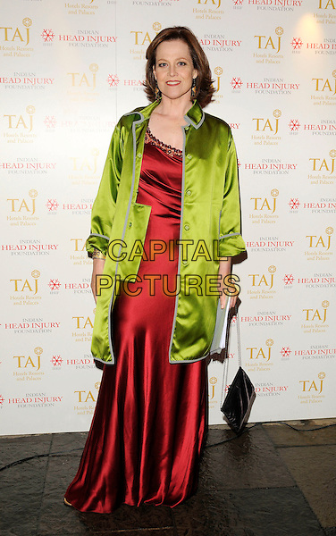 SIGOURNEY WEAVER.At the Royal Rajasthan gala dinner, Banquetting House, Whitehall, London, England, UK, November 9th 2009..full length green coat silk satin red long maxi dress burgundy  bag coat jacket .CAP/CAN.©Can Nguyen/Capital Pictures.