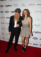 Aug. 29, 2013; Avon, IN, USA: ZZ Top guitarist/vocalist Billy Gibbons (left) walks the red carpet with wife Gilligan Stillwater prior to the premiere of Snake & Mongoo$e at the Regal Shiloh Crossing Stadium 18. Mandatory Credit: Mark J. Rebilas-