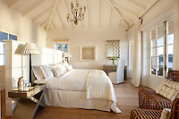 A spacious bedroom in neutral tones with a wood floor and french doors. The room has a king size bed and a dressing table and chair in the corner. A chandelier hangs from a pitched beamed ceiling and lamps stand on modern bedside tables.