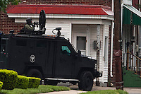 SWAT team officers points a gun outside a house where an armed man with multiple hostages is barricaded in a standoff that began Friday afternoon. Trenton New Jersey, May 11, 2013. by Kena Betancur / VIEWpress