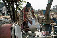 Rani barukaum, the SHG group leader uses the municipal water to wash utensils outside her house in Ambedkar Nagar in Medak, Telangana, India.