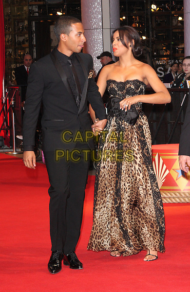 """MARVIN HUMES & ROCHELLE WISEMAN.""""Water For Elephants"""" UK film premiere,.Vue Westfield, Upper Level, Westfield Shopping Centre, White City, London, England, UK..May 3rd 2011.full length couple JLS the Saturdays black suit long maxi leopard print dress brown animal side lace clutch bag  profile holding hands tongue.CAP/ROS.©Steve Ross/Capital Pictures."""