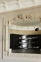 The elegantly curved lines of the contemporary kitchen cupboards are reflected in an ornate 19th century mirror