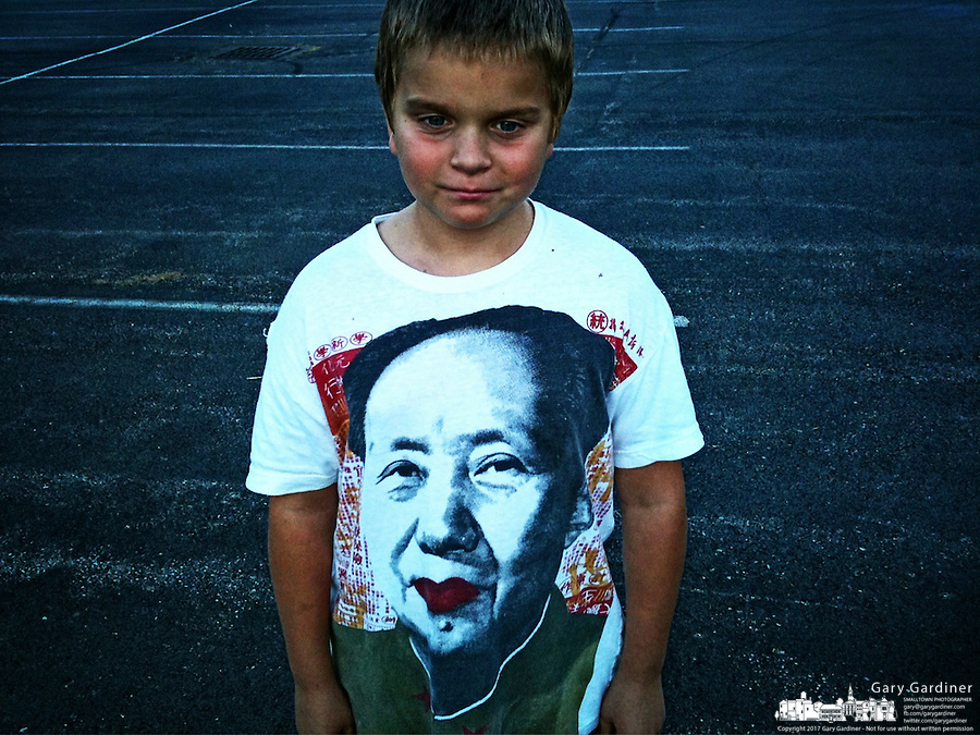 Young boy wearing a chairman Maoe t-shirt stands in a church parking lot at the conclusion of a day-long car show.