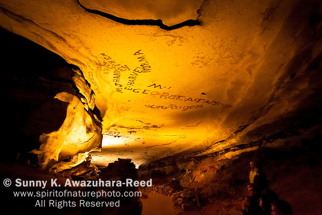 Visitors looking at the historic smoke signatures on the cave ceiling, Gothic Avenue, Mammoth Cave National Park, Kentucky.