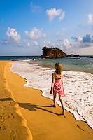 Tourist walking on Mirissa Beach, South Coast of Sri Lanka, Asia. This is a photo of a tourist walking along Mirissa Beach, Sri Lanka, Asia. Mirissa Beach is a popular sandy tourist beach on the South Coast of Sri Lanka.