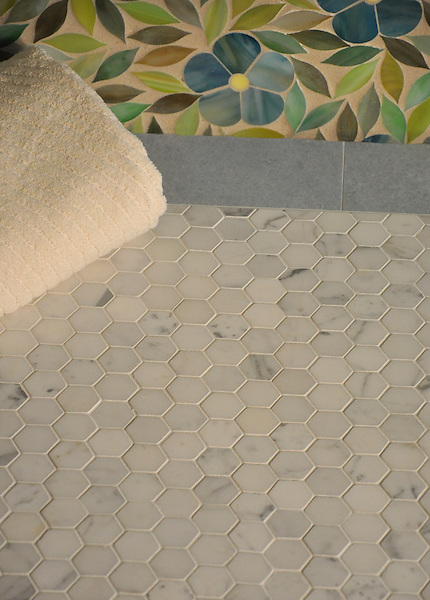 "Jacqueline, a jewel glass waterjet mosaic shown in Alexandrite, Emerald, Citrine and Peridot, is part of the Silk Road® collection by New Ravenna. This pattern is shown with 2"" x 6"" Celeste base moldings and a 3 cm Hex in Statuary Carrara floor."