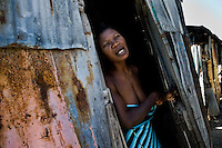 A Haitian woman stands in the door of a shack in the slum of Cité Soleil, Port-au-Prince, Haiti, 11 July 2008. Cité Soleil is considered one of the worst slums in the Americas, most of its 300.000 residents live in extreme poverty. Children and single mothers predominate in the population. Social and living conditions in the slum are a human tragedy. There is no running water, no sewers and no electricity. Public services virtually do not exist - there are no stores, no hospitals or schools, no urban infrastructure. In spite of this fact, a rent must be payed even in all shacks made from rusty metal sheets. Infectious diseases are widely spread as garbage disposal does not exist in Cité Soleil. Violence is common, armed gangs operate throughout the slum.