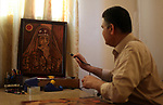 Medical Laboratory specialist Mohamed El Sherif, 54, displays a drawing of burned wood at his house, in Gaza city, on May 16, 2019. El Sherif has drawing talent, take it as a paint since four years, and participat in many exhibitions. Photo by Mahmoud Ajjour
