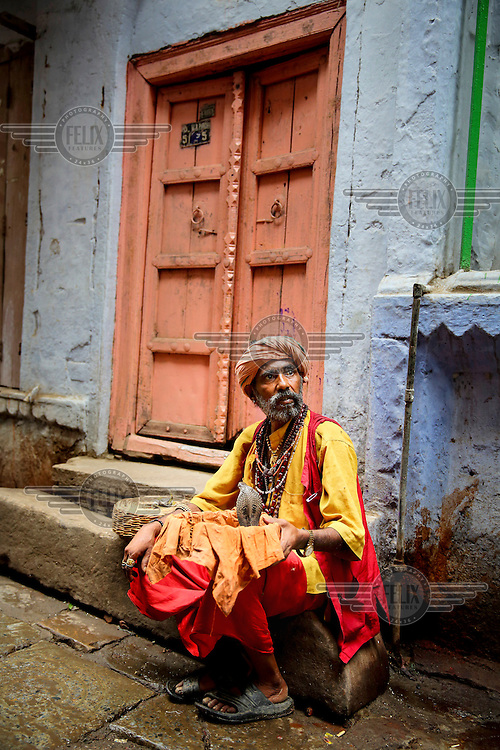 A snake charmer sits at the side of the street with a cobra emerging from a basket on his lap.