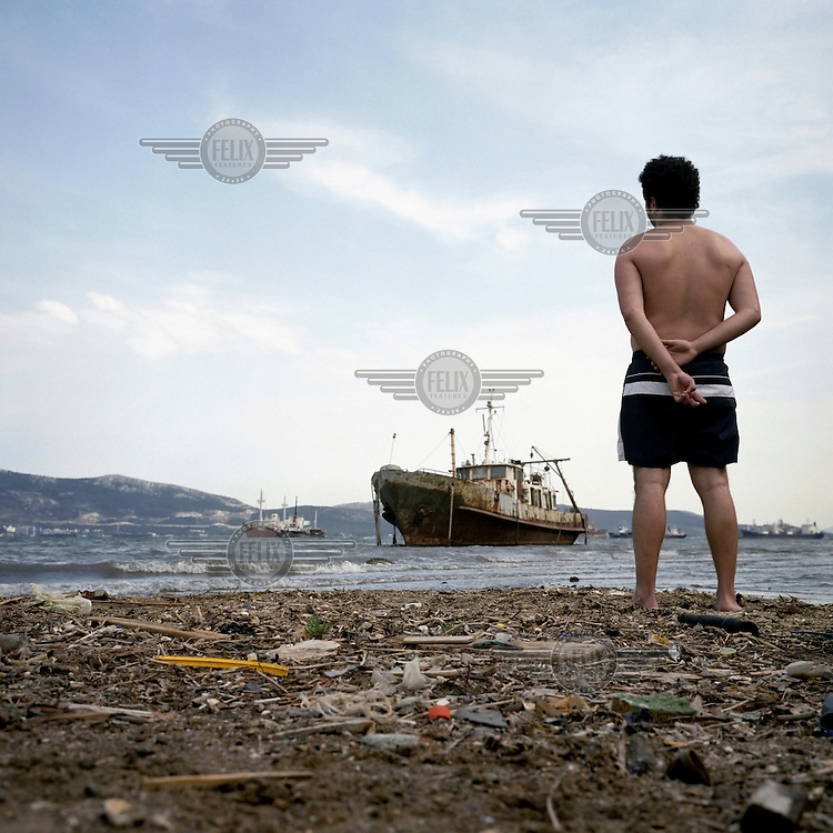 A man stands on the shore next to the Halyvourgiki Inc steel factory. The water around the town is not safe for swimmers as it is heavily polluted by waste from nearby shipyards, oil refineries, cement factories and tanneries.