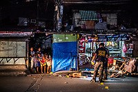 "MANILA, PHILIPPINES - OCTOBER 02: Scene of The Crime polie investigators, SOCO, conduct their investigation as the body of Michael Araja, 29, an alleged drug user lays in front of ""sari sari"" a local convenience store, after being gunned down in the street by unidentied men in a ""riding-in-tandem"" killing in the early hours of October 02, 2016 in Manila, Philippines. According to neighbors, two unidentified men on a motorcycle, stopped as Mr Araja, had left his home to buy cigarettes and a drink for his wife, and gunned him down as he stood in front of his local convenience store. This type of murder perpetrated two peope on a motobike, is commonly referred to as a ""riding-in-tandem"" killing.  <br /> Photo by Daniel Berehulak for The New York Times"