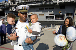 Lt.Cmdr. Michael Morgan holds his two sons, Mikey and Corey as he and his wife Courtney departs the USS John C. Stennis after it arrived on July 10, 2009 at Naval Station Kitsap in Bremerton, WA.  The carrier and it's 3,200 crewmembers arrived Friday after spending a six-month deployment in support of  Middle East operations. (© Jim Bryant Photo. All Rights Reserved