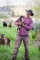 Farmer, Paul Kaiser with day old lamb, Soay sheep (Ovis aries) at Singing Frogs Farm