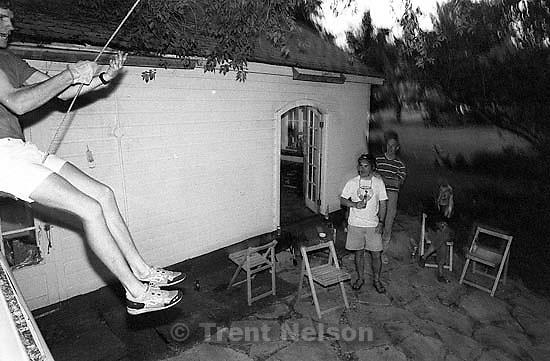 Steve Griffin on the swing at Todd Crosland's house. Todd Crosland, Rick Egan, Kristan Jacobsen on ground.<br />