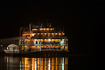 The small riverboat casino on the riverfront in Clinton, IA is lit up at night and reflecting in the calm waters of the Mississippi River.