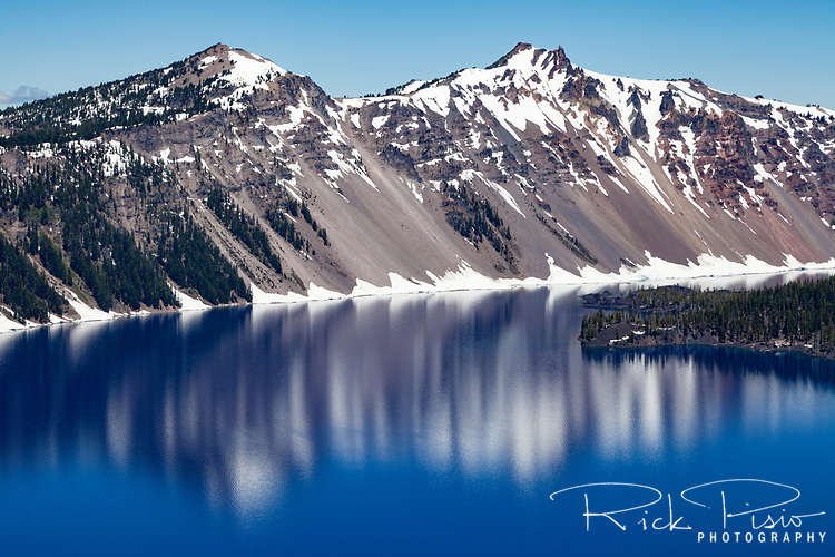 The north rim of Crater Lake reflects in the waters of Crater Lake National Park in Oregon.