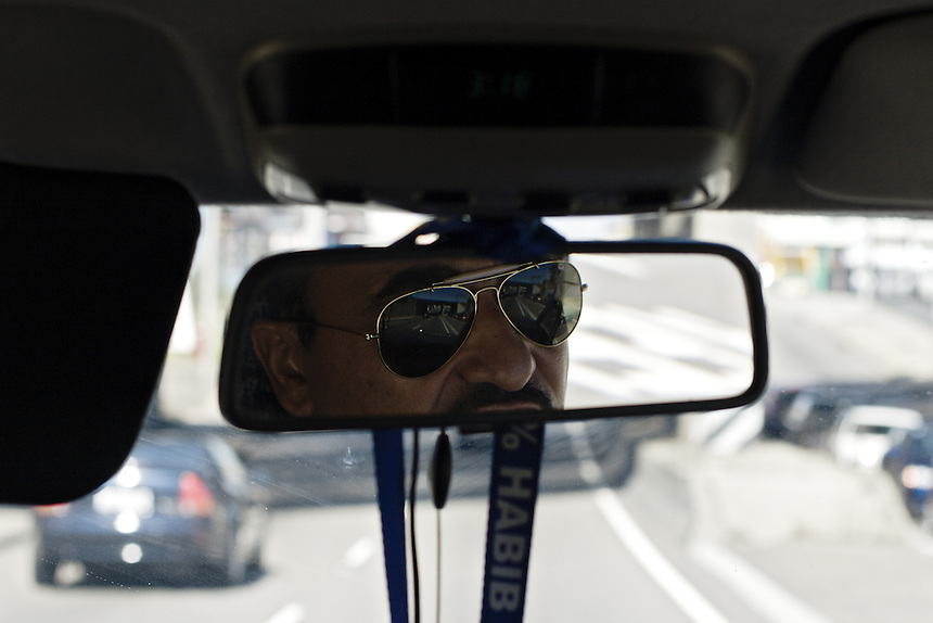 Habib is reflected in a rear view mirror while driving through western Sydney, March 2007.