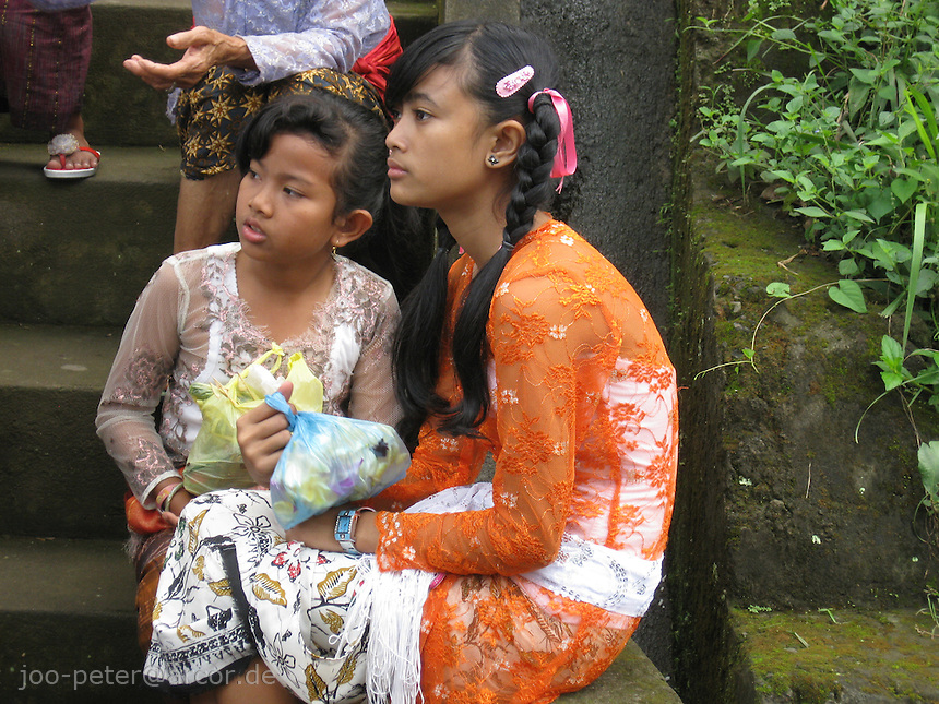 girls waiting for the procession of cremation day to start, village Laplapan,  Bali, archipelago Indonesia