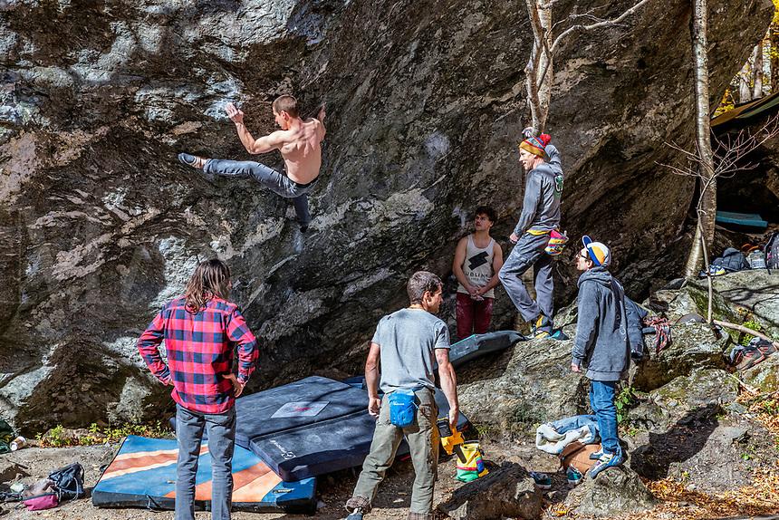 Guys practice rock climbing on natural boulder at Smuggler's Notch State Park.