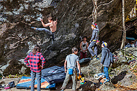 Guys practice rock climbing on natural boulder at Smuggler's Notch State Park.