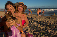 Priscila (cq) Cury kisses dog Luma while enjoying the last rays of sun on the playa brava beach in Punta del Este, Uruguay, with fellow Brazilian Maria Elenah (cq) Serpa. The venerable South American beach resort is having a rennaisance. (Kevin Moloney for the New York Times)
