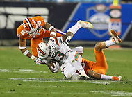 Charlotte, NC - December 2, 2017: Miami Hurricanes running back DeeJay Dallas (13) gets tackled by several Clemson Tigers defender during the ACC championship game between Miami and Clemson at Bank of America Stadium in Charlotte, NC. Clemson defeated Miami 38-3 for their third consecutive championship title. (Photo by Elliott Brown/Media Images International)