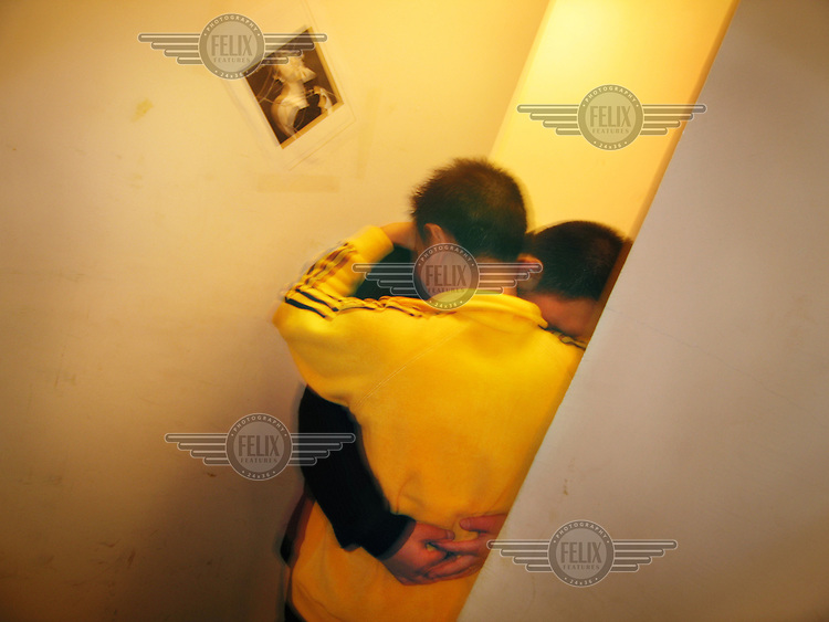 Two young men hug each other at a meeting centre for homosexuals that is run by a local Chinese NGO.  The situation regarding homosexuality in China is ambiguous, as it is neither condoned, nor ouvertly castigated.